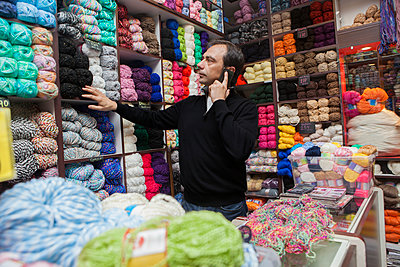 Mixed Race man talking on cell phone at yarn store - p555m1491163 by REB Images