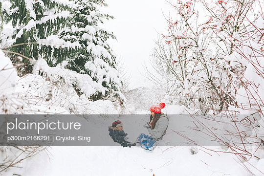 Woman playing with baby in winter landscape, Canada - p300m2166291 by Crystal Sing