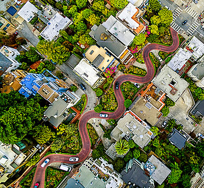 Aerial view of a residential city area, with road descending a hillside with eight hairpin turns.  - p1100m1216194 by Mint Images