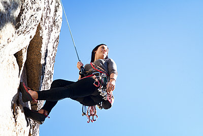 Low angle view of woman rappelling against clear blue sky - p1166m1231441 by Cavan Images
