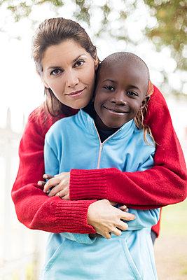 Portrait of mother embracing son at park - p1166m1530826 by Cavan Images