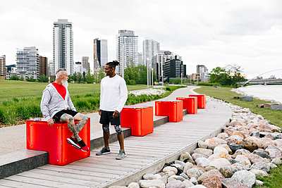 Mature male runners talking in urban park - p1192m2109999 by Hero Images