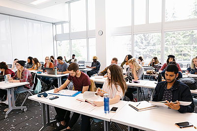 Students sitting at desks in university classroom - p1192m2110100 by Hero Images