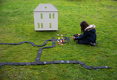 Girl playing with dollhouse and toy cars - p1231m2245495 by Iris Loonen