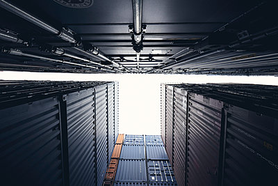 Stacked storage containers, worm's eye view - p1696m2296601 by Alexander Schönberg