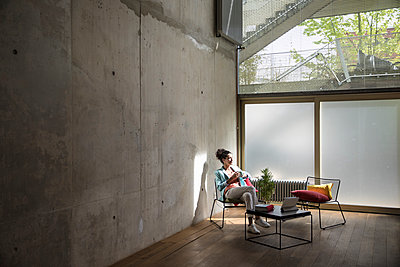 Businesswoman sitting in a loft at concrete wall having a break - p300m2079559 by Florian Küttler