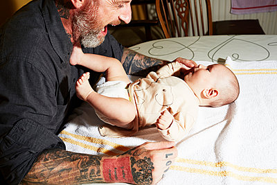 Father entertaining baby son lying on living room table - p429m958273 by JPM