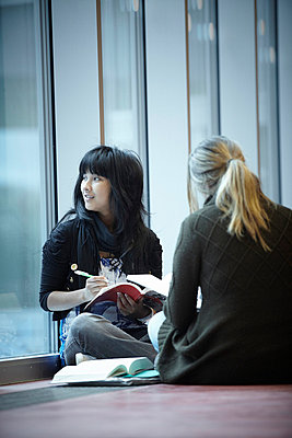 Two teenage girls studying in corridor - p528m718659f by Morgan Karlsson