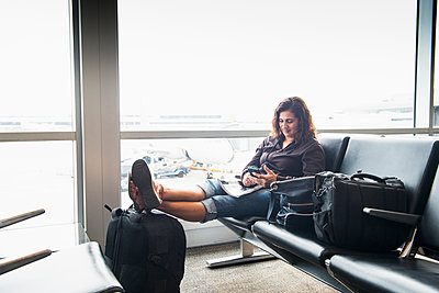 Hispanic woman texting on cell phone in airport - p555m1410120 by Sollina Images