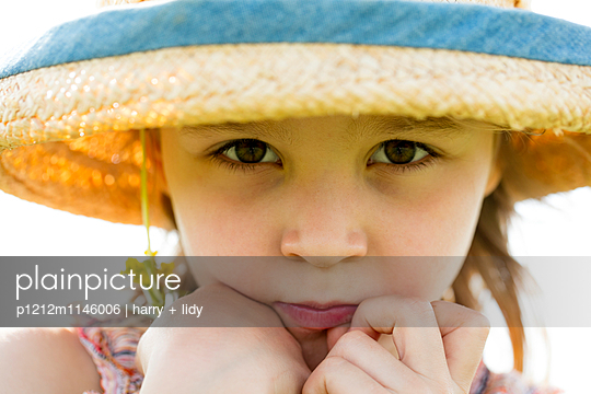 Mädchen mit Sonnenhut und kleine Blumen - close - p1212m1146006 von harry + lidy