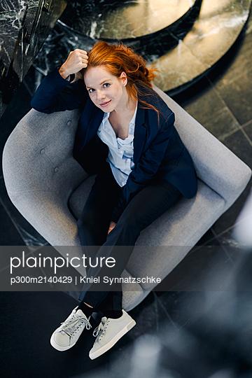 Top view of businesswoman sitting in armchair - p300m2140429 by Kniel Synnatzschke