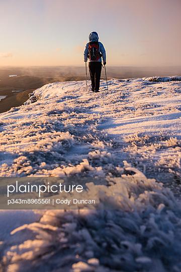 Female hiker at sunrise on winter summit of Pen Y Fan - p343m896556f by Cody Duncan