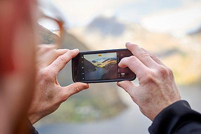 Mann fotografiert Geirangerfjord mit Smartphone - p1124m1503396 von Willing-Holtz