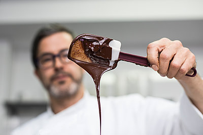 Chef looking at chocolate cream in a spatula - p1166m2130236 by Cavan Images