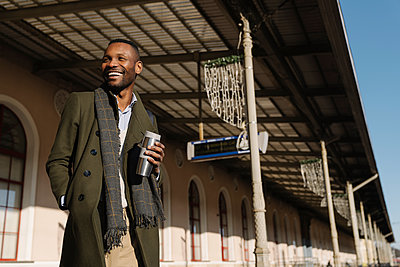 Happy stylish man with reusable cup waiting for the train - p300m2154584 by Hernandez and Sorokina