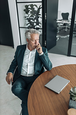 Thoughtful businessman sitting on chair by table at office - p300m2226103 by Gustafsson