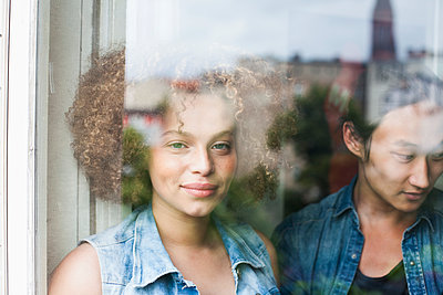 Portrait of smiling woman standing with man seen through glass window - p301m1535056 by Larry Washburn