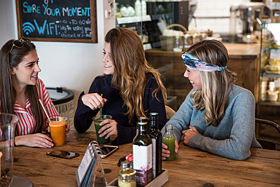 Three young female friends with vegetable juice chatting in cafe - p429m1578655 by RUSS ROHDE