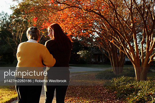 Rear view of senior woman and adult daughter strolling in suburban park - p1427m2283186 by Roberto Westbrook