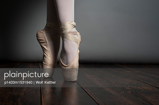 Female en pointe feet to above ankles on wooden floorboards. - p1433m1531940 by Wolf Kettler