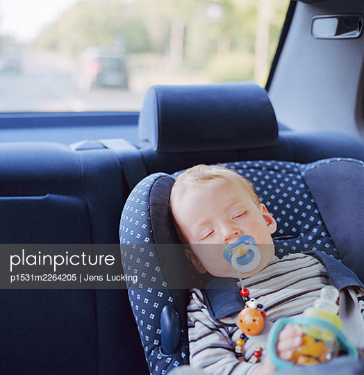 Baby boy (6-9 months) sleeping in car seat in luxury car - p1531m2264205 by Jens Lucking