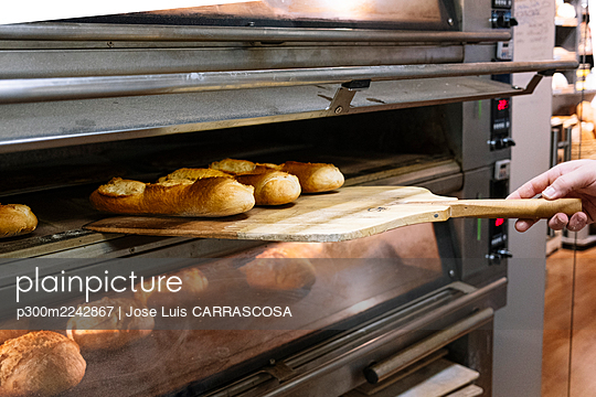 Male chef taking out freshly baked bread with pizza peel from oven at bakery - p300m2242867 by Jose Luis CARRASCOSA