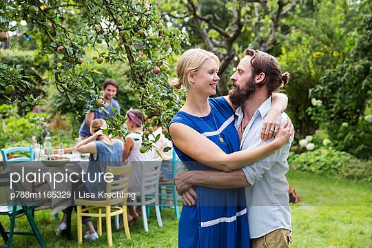 Paar umarmt sich im Garten - p788m1165329 von Lisa Krechting