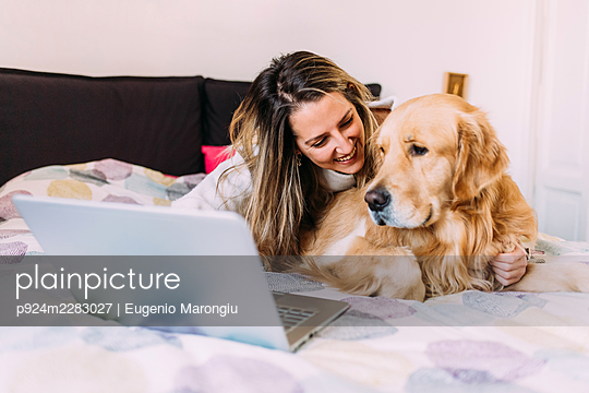 Italy, Young woman with dog on bed looking at laptop - p924m2283027 by Eugenio Marongiu