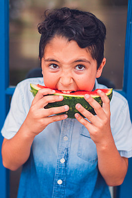 Close-up portrait of boy eating watermelon while standing outdoors - p1166m2112043 by Cavan Images
