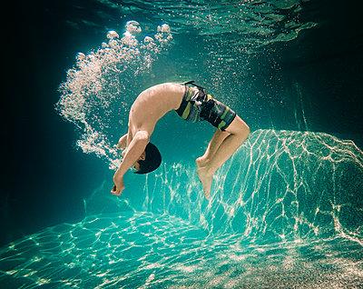 Underwater image of teenage boy doing a flip underwater. - p1166m2138076 by Cavan Images