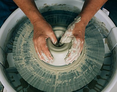 hands shaping pottery on a wheel with messy hands in a studio - p1166m2285739 by Cavan Images