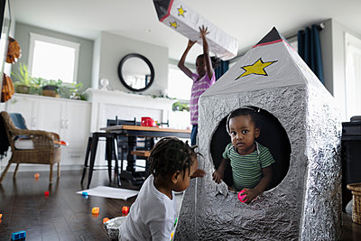 Brothers playing with toy spaceship in living room - p1192m2046986 by Hero Images