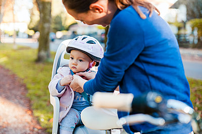 Mother and daughter riding bicycle, baby wearing helmet sitting in children's seat - p300m2059880 by Daniel Ingold