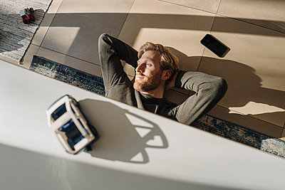 Relaxed man lying on the floor at home - p300m2167242 by Kniel Synnatzschke