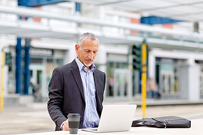 Businessman working on laptop at railroad station - p300m2287537 by Emma Innocenti