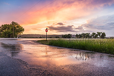 Sunset reflected on wet highway, Montana, US - p429m1547812 by SuHP