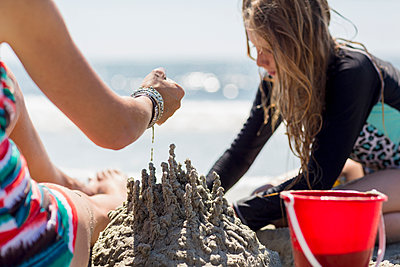 Caucasian mother and daughter playing with sand castle at the beach - p555m1522753 by Marc Romanelli