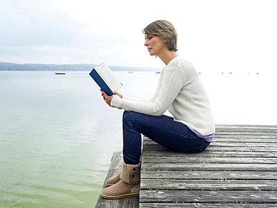 Frau liest Buch auf einem Steg  - p6430081 von senior images