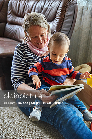 Grandmother and grandson with children's book - p1146m2187833 by Stephanie Uhlenbrock