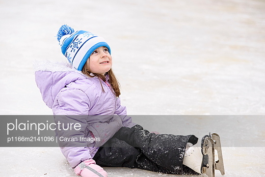 Little Girl Sitting Down on Ice While Skating - p1166m2141096 by Cavan Images