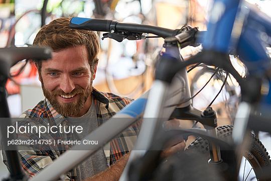 Mechanic repairing bicycle in workshop - p623m2214735 by Frederic Cirou