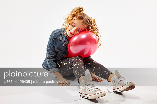 Blonde girl with red balloon - p968m1128435 by roberto pastrovicchio