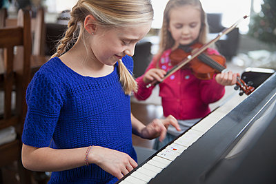 Young sisters practising music together - p1192m1219200 by Hero Images