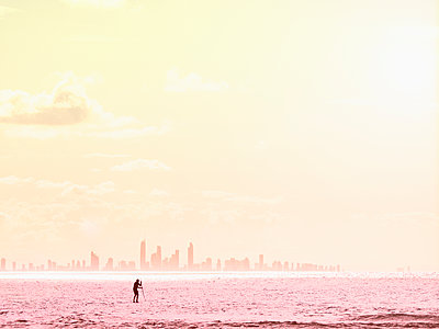 Silhouette of man paddleboarding on sea at sunset - p1427m2038158 by WalkerPod Images