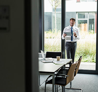 Businessman with atomic model and tablet in his office - p300m2043014 by Uwe Umstätter