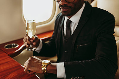 Businessman holding champagne in private jet - p300m2256405 by OneInchPunch