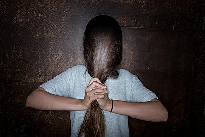 Woman hiding face behind hair - p427m1194979 by Ralf Mohr