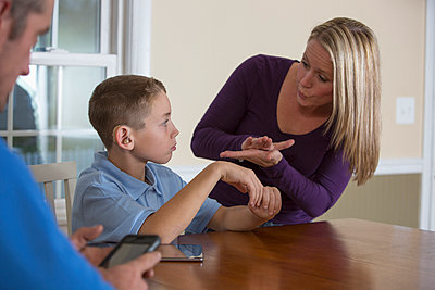 Caucasian mother signing with deaf son - p555m1305699 by Disability Images