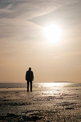 Silhouette man standing on beach with low sun - p597m2055251 by Tim Robinson
