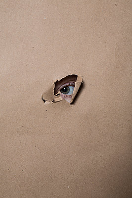 An eye peeking through a small hole in a paper   - p847m1152007 by Johan Strindberg